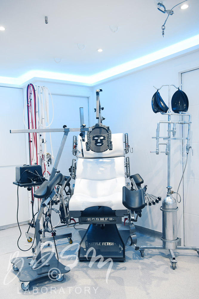 BDSM bondage chair with face mask and kink kit