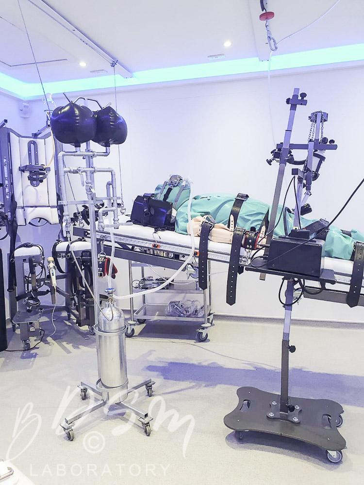 A slave strapped to a bench with loads of BDSM kink equipmentat the BDSM Laboratory