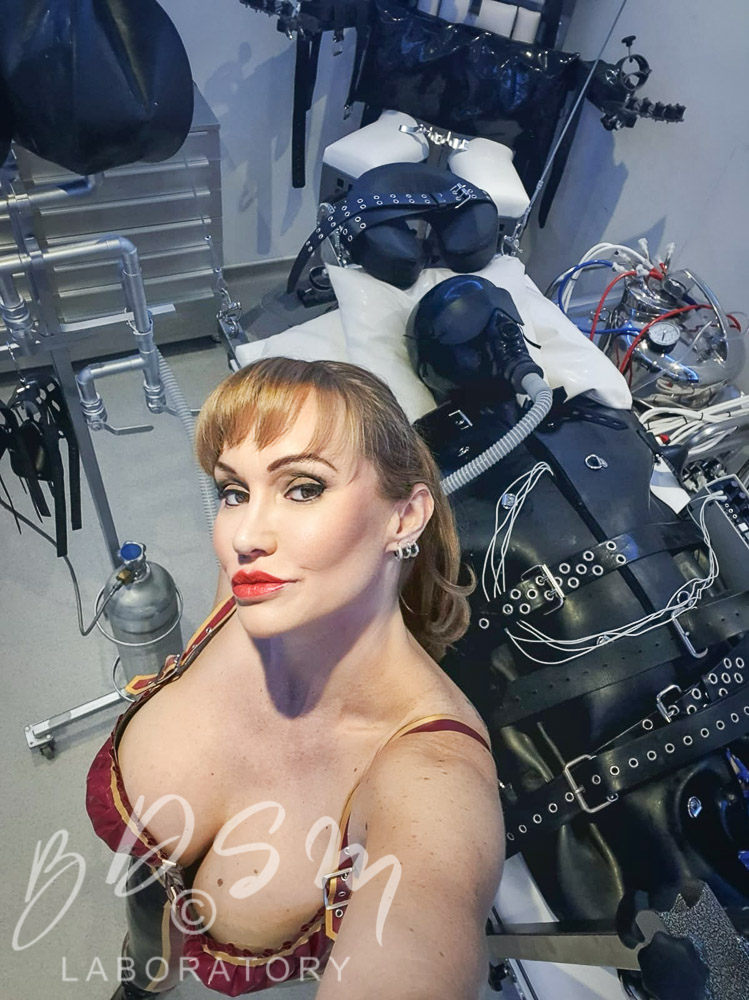 Mistress Miranda and a caaptive submissive buckled to a bench in black latex at The BDSM Laboratory