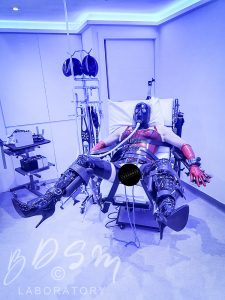 Slave wearing a rubber mask and breathing tube and strapped into BDSM chair