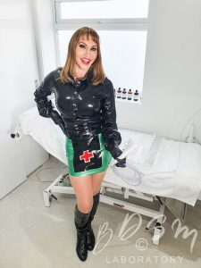 Mistress Miranda in a black and green latex nurse outfit