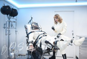 Mistress Miranda with a sub bound to a BDSM chair at The new BDSM Laboratory fetish kink extravaganza