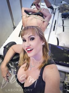 Mistress Miranda in front of sub secured with Shibari rope bondage