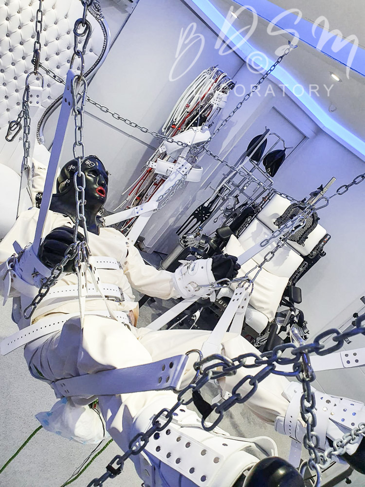 Slave in a bondage sling chained to the ceiling
