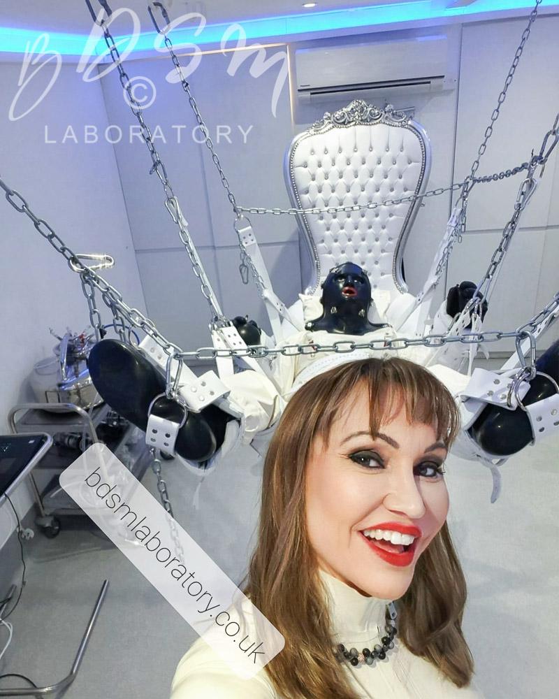 Mistress Miranda smiling with the bondage sling in teh background